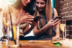 Two cheerful girlfriends using phone looking at screen smiling while having breakfast at coffee house