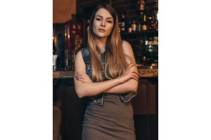 Portrait of young female model with fair hair leaning her elbows on bar counter looking at camera in vintage restaurant