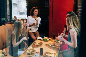 Four cheerful girlfriends having fun chatting and laughing eating and drinking in fast food restaurant