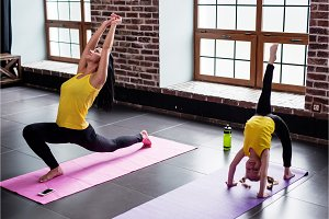 Young woman and little girl doing gymnastic stretching exercises on mat in fitness studio