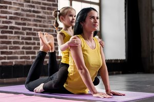 Young happy mother doing stretching exercise on mat while her smiling daughter hugging her in sports club