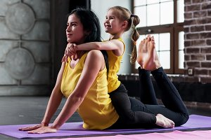 Young Caucasian woman doing stretching exercise for spine together with a child sitting on her back in gym