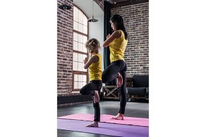 Mother and daughter wearing sports clothing practicing yoga together meditating standing on one leg with hands in prayer position in loft apartment
