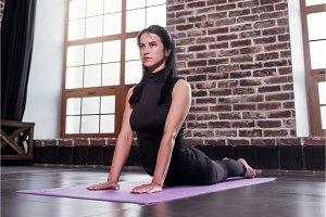 Female yoga beginner doing bhujangasana cobra pose on mat in loft apartment