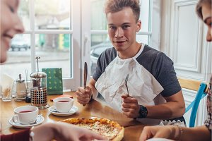 Stylish teenager wearing napkin holding knife and fork ready to eat pizza sitting against window at restaurant