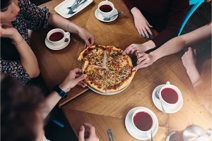 Top view of family members having lunch reaching out for pizza pieces in pizzeria
