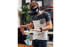 Amazed young man wearing virtual reality goggles playing an interactive game trying to touch something at home