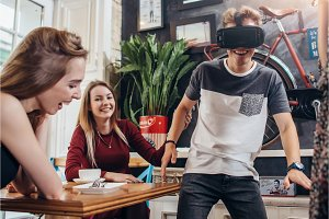Teenagers passing leisure time by testing virtual reality helmet playing funny games at home