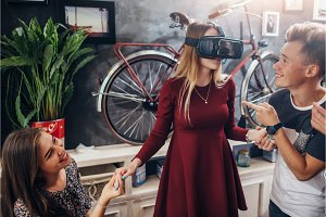 Group of cheerful students supporting their female friend playing funny game using virtual reality helmet in living room