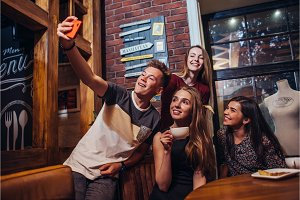 Group of smiling attractive teenagers wearing casual outfit taking selfie with mobile phone drinking tea in a cafe with loft interior