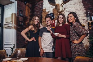 Four cool teenagers wearing casual clothes posing for camera in a stylish with hunting lodge interior design.