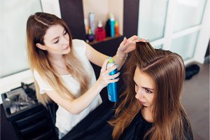 Professional hairdresser using hair spray working on young girl s hair in beauty salon