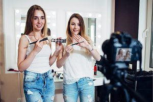 Two beauty bloggers filming a makeup shopping guide demonstrating eyeshadows and brushes against make up mirrors in studio