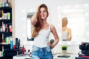 Portrait of cheerful hair stylist wearing casual clothes standing in hairdressing salon