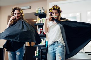 Two female friends goofing around in front of the camera making moustache from hair and curler standing in flying cape like heroes at beauty shop
