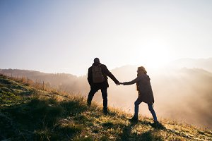 Senior couple on a walk in an autumn nature at sunrise.