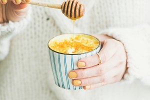 Turmeric latte, golden milk with honey in woman's hands