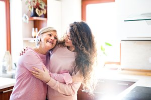 A teenage girl with mother at home, hugging.