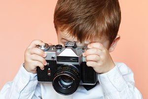 Little boy with aged retro camera.