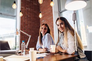 Portrait of two pretty smiling young women looking at camera sitting at work desk. Female freelancers working at home