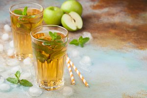 Two glasses of green Apple juice with mint and ice on an old rusty table. Soft drink on a blue background. With copy space