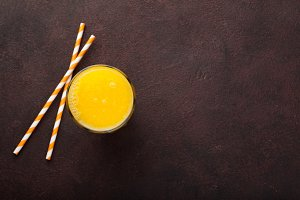 A glass of freshly squeezed orange juice and straws for juice on a dark brown background. Top view with copy space