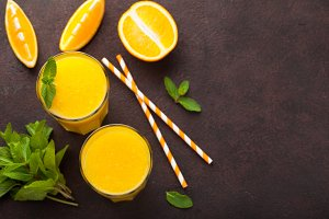 Two glasses of freshly squeezed orange juice and mint on a dark brown background. Top view with copy space