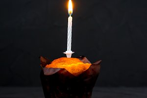 The candle burns on a cake on black background.
