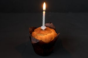 A cake with a candle on black background. The candle of mourning is burning.