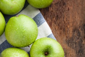 Ripe green apples in a wooden bowl on an old rustic table. Useful fruits on wooden background. Top view