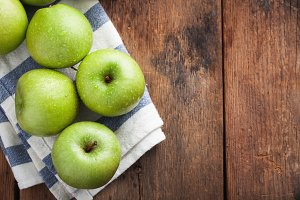 Ripe green apples in a wooden bowl on an old rustic table. Useful fruits on wooden background. Top view with copy space