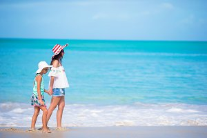 Beautiful mother and daughter on Caribbean beach. Family on beach vacation
