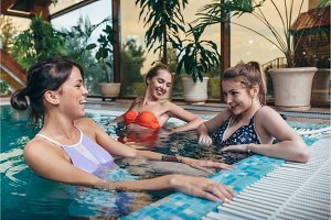 Group of girlfriends having fun in the indoor swimming pool in spa center