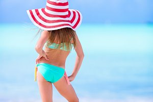 Adorable little girl in big hat on the beach