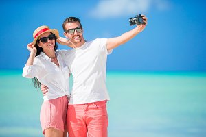 Happy couple taking a selfie photo on white beach. Two adults enjoying their vacation on tropical exotic beach