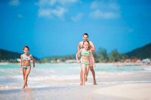 Father and little kids enjoying beach summer tropical vacation. Family playing on the beach