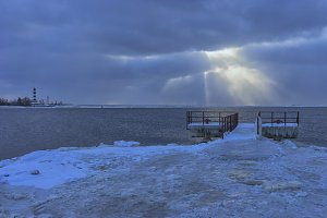 Wharf in winter at the mouth of the river with a beacon