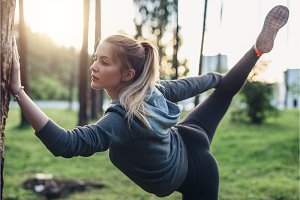 Female athlete doing leg hold pose stretching exercise standing on one leg in city park