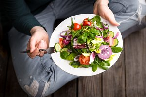 Fresh salad in hands view from above