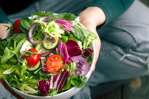 Fresh salad in hands view from abov…