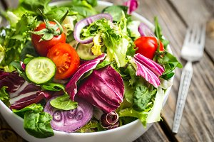 Fresh salad on a wooden background