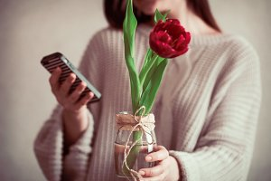 Girl with tulip and phone in hands