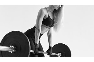 Fit young woman lifting barbell