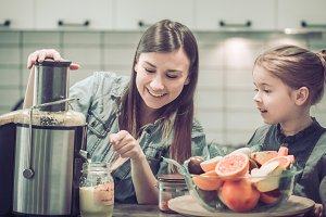 Mom with children in the kitchen prepares juice fresh