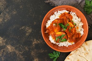 Chicken korma with a spicy sauce over white rice.Traditional Indian dish on a rustic background. Top view, copy space.