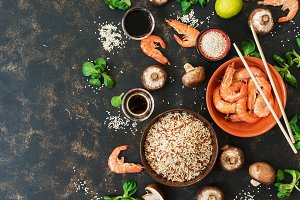 Background with ingredients of Asian cuisine brown rice, shrimp and mushrooms. Top view, copy space