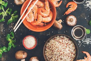Raw brown rice with shrimps and mushrooms, Asian cuisine. Cooking. The concept of healthy eating. View from above. Toned.