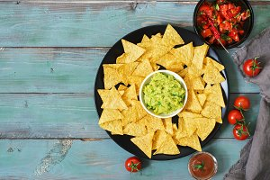 Nachos. Mexican food. Corn chips with sauce of salsa and guacamole on a green blue rustic background. Top view.