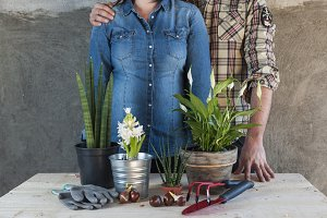Man and woman with flowers and tools