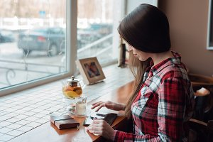 The brunette girl with long beautiful hair in her shirt, in the afternoon at a cafe by the window, looks at the mobile tablet. Next to the table is a paper bag. A teapot with a mug of tea.